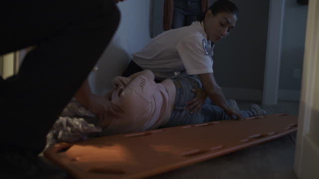 paramedics sliding stretcher underneath injured girl laying on floor / lehi, utah, united states - lehi stock videos & royalty-free footage