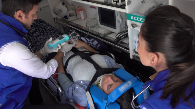 paramedics taking vital signs of a patient - emergency services vehicle stock videos and b-roll footage