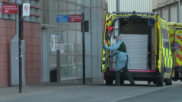 paramedics wear ppe as they transfer a patient as a line of ambulances build up outside the royal london hospital in east london on january 3, 2021.... - exchanging stock videos & royalty-free footage