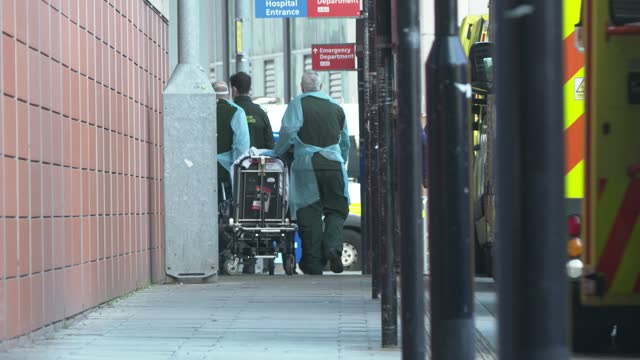 paramedics wearing full ppe take a patient into the hospital as a line of ambulances build up outside the royal london hospital in east london on... - shape stock videos & royalty-free footage
