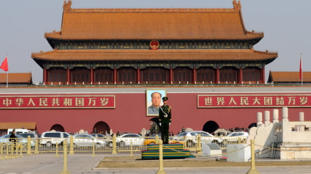 a paramilitary police officer stands guard in front of a portrait of late communist leader mao zedong at the great hall of people on march 05 2017 in... - chinese flag stock videos & royalty-free footage