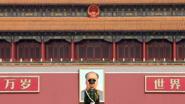 vídeos de stock, filmes e b-roll de a paramilitary police officer stands guard in front of a portrait of late communist leader mao zedong at the great hall of people on march 05 2017 in... - portão da paz celestial de tiananmen