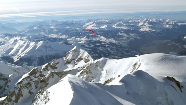 ws aerial ts paramotor turning towards the summit of the mont blanc / chamonix, haut savoir, france  - schneebedeckt stock-videos und b-roll-filmmaterial