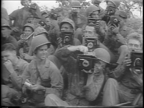 paramount cameraman damien parer shooting with handheld camera / montage of combat footage from pacific theater combat cameramen pose with their... - cameraman stock videos & royalty-free footage