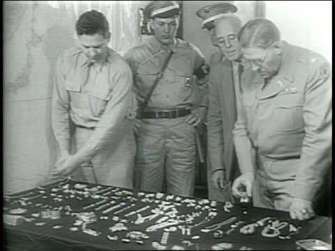 / paramount newsreel / hessian jewel robbery / at the illinois central depot, an mp soldier looks at the baggage lockers where the jewels were found... - 荒い麻布点の映像素材/bロール