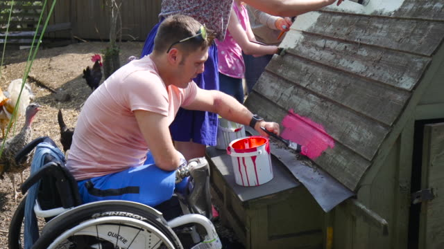 paraplegic helping to paint chicken shed - community stock videos & royalty-free footage