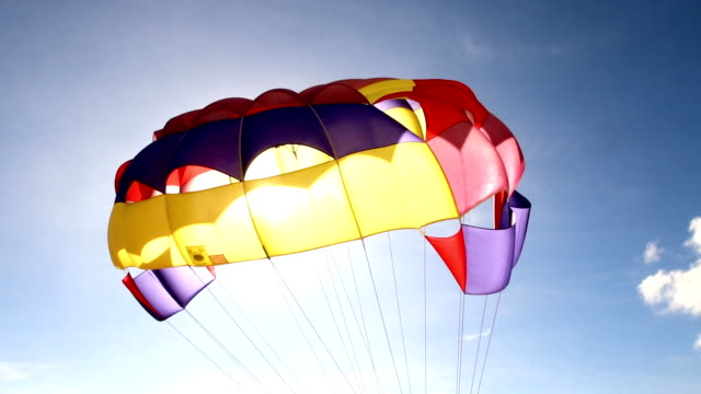 parasail schwebend in der luft gegen den blauen himmel - fallschirm stock-videos und b-roll-filmmaterial