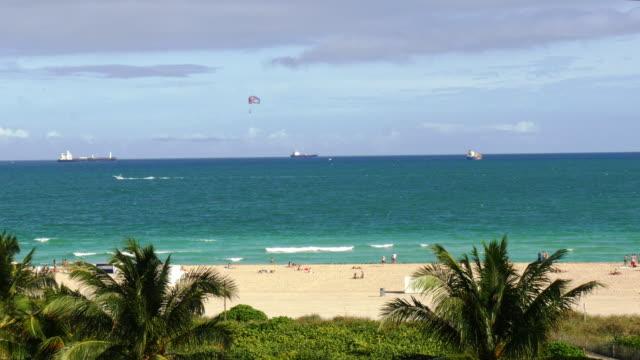 parasail passing by miami beach, south beach. wide shot - spoonfilm stock-videos und b-roll-filmmaterial
