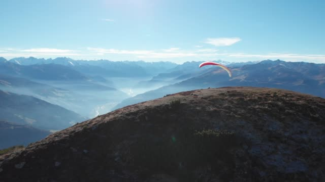 parasailer takes flight over mountains, lakes, forests - 達成点の映像素材/bロール