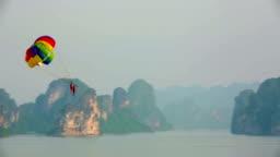 Parasailing over limestone mountain islands, Halong Bay, Vietnam