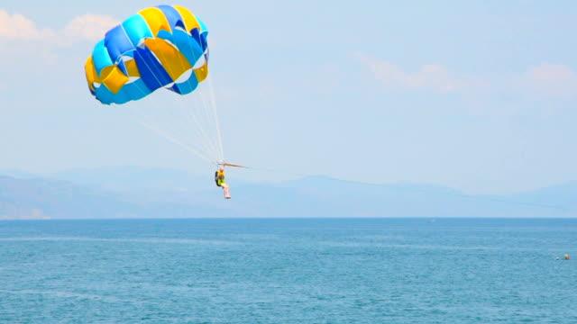 vídeos de stock, filmes e b-roll de parasail sobre o mar - paraquedismo
