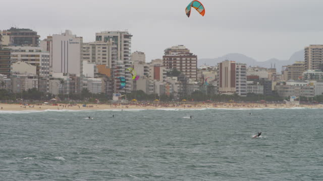 Parasailing surfer is distance from shore and goes under.