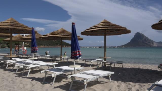 pan / parasol of straw on sandy beach - sassari stock videos & royalty-free footage