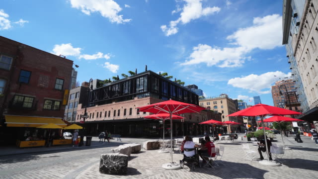 parasols and tables are set on the public space at gansevoort plaza in meatpacking district. people can be enjoying to eating food and drinking in... - stato di emergenza video stock e b–roll