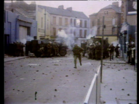 paratroopers at william street roadblock fire tear gas and rubber bullets to disperse demonstrators immediately prior to bloody sunday shootings... - ロンドンデリー点の映像素材/bロール