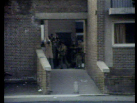 paratroopers enter block of flats in bogside to make arrests and line suspected rioters against wall bloody sunday londonderry 30 jan 72 - ロンドンデリー点の映像素材/bロール