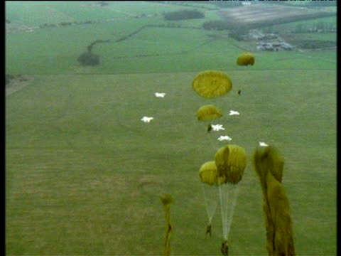 vídeos y material grabado en eventos de stock de paratroopers jump out of aeroplane over salisbury plain. parachutes open and fall in jelly-fish like shapes. - soldado paracaidista