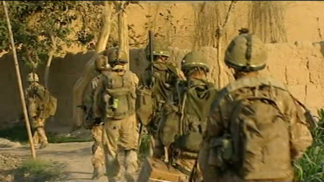 Paratroopers return from Afghanistan T15090820 Helmand Province EXT Paratroopers from 2nd Battalion Parachute Regiment sheltering behind wall as...