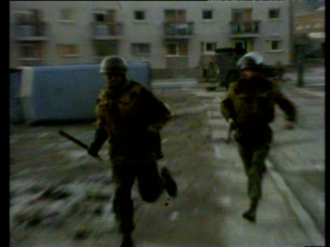 paratroopers run across open ground in rossville flats estate pursuing rioters bloody sunday londonderry 30 jan 72 - ロンドンデリー点の映像素材/bロール