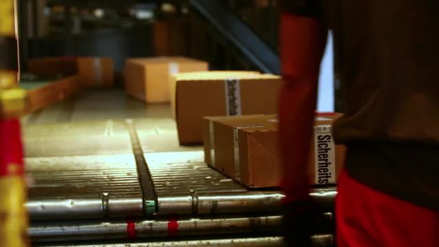 stockvideo's en b-roll-footage met cu parcels loaded onto conveyor belt in a parcel distribution center  - middelgrote groep dingen
