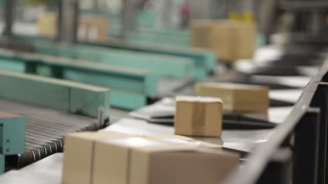vidéos et rushes de parcels move along conveyors at a dhl parcel center operated by deutsche post ag in saulheim germany on thursday feb 18 a parcel is illuminated by a... - post it