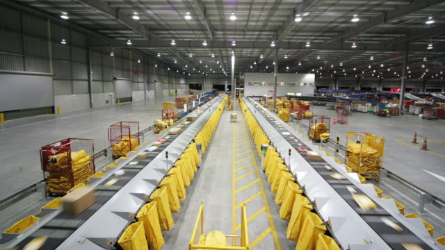vídeos y material grabado en eventos de stock de t/l ws ha parcels on conveyer being sorted into mail bags, auckland, new zealand - perspectiva en disminución