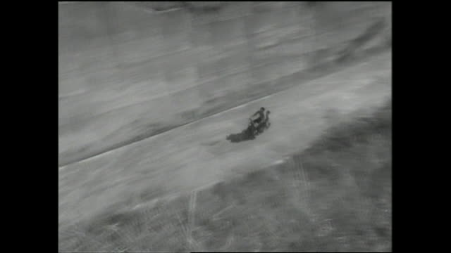 A parent and child ride a motorbike into a tunnel.