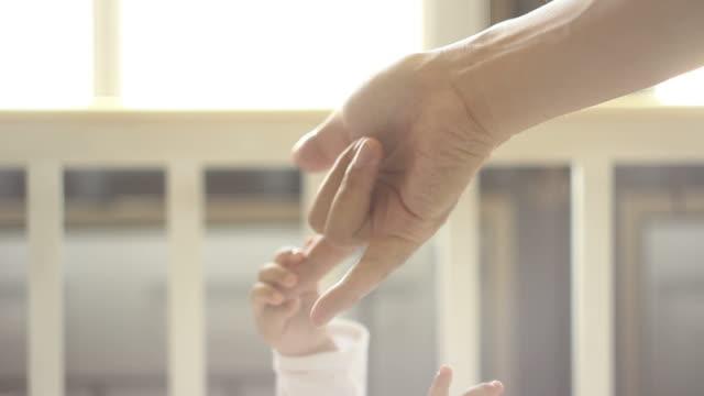 vídeos de stock, filmes e b-roll de hd: pai segurando o bebê mãos - agarrar