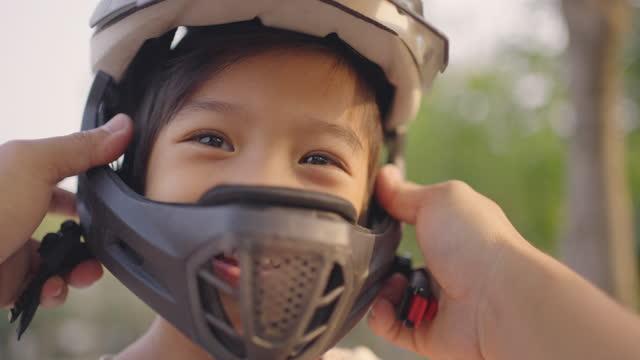 vídeos de stock, filmes e b-roll de pai colocando capacete esportivo para seu menino feliz. - capacete esportivo