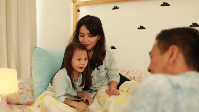 parent reading a book to their daughter - bedclothes stock videos & royalty-free footage