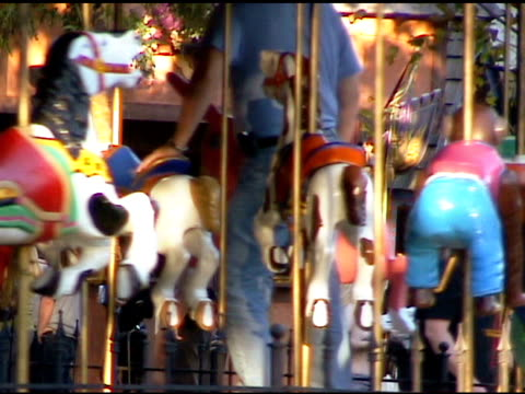 parent riding merry go round carrousel with child - carousel horse stock videos and b-roll footage