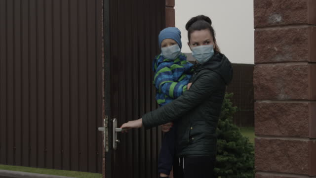 parent with child closing door wearing face masks a concept of self-isolation and social distancing because of pandemia of coronavirus covid-19 - social distancing stock videos & royalty-free footage