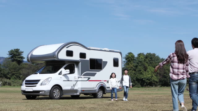 parents and children embracing each other in front of camper trailer - camper trailer stock videos and b-roll footage