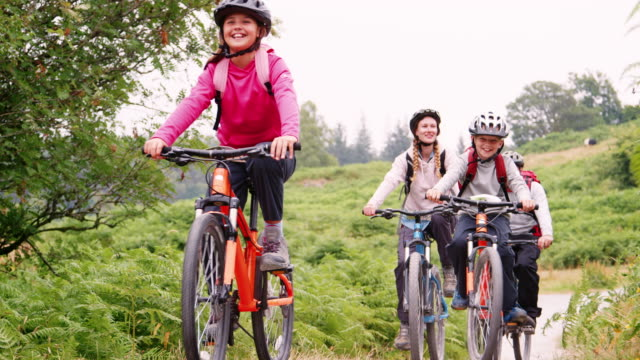 Parents and children riding mountain bikes on a country path during a family camping holiday, Lake District, UK