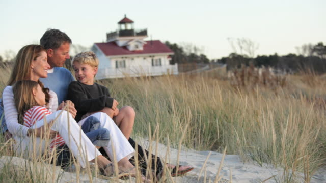 ws pan parents and children sitting in front of beach house on dunes / eastville, virginia, usa - beach house stock videos & royalty-free footage