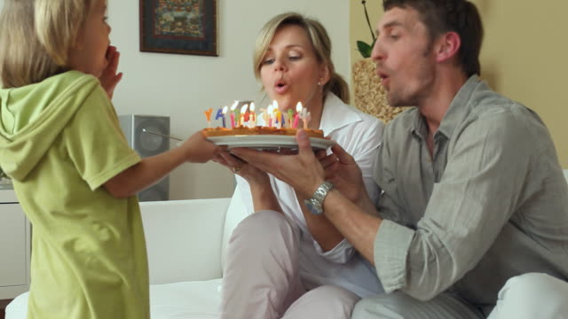 vidéos et rushes de ms ds parents and daughter (4-5) blowing out candles on birthday cake / potsdam, brandenburg, germany - anniversaire