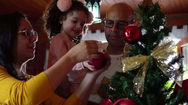 vidéos et rushes de parents et descendant décorant l'arbre de noël - 35 39 years