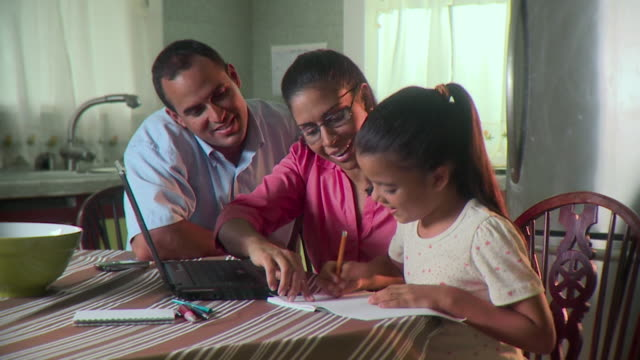 ms parents and daughter (6-7) doing homework on kitchen table, panama city, panama  - panama city panama stock videos & royalty-free footage