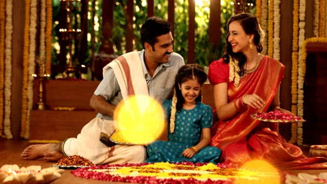 MS Parents and daughter making flower rangoli during pongal festival / New Delhi, India