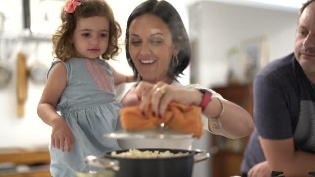 vídeos de stock, filmes e b-roll de pais e filha que preparam a pipoca em casa - etnia caucasiana