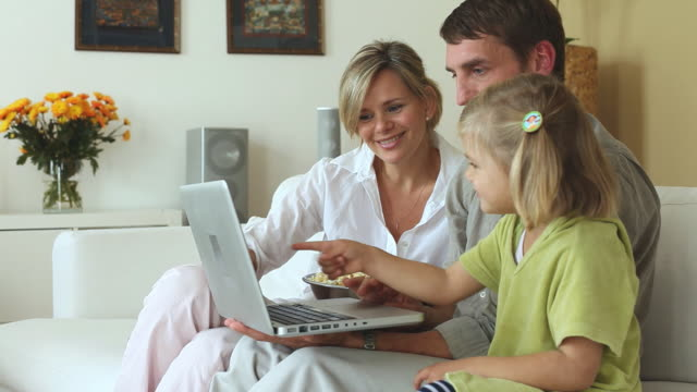 ms parents and daughter (4-5) sitting on sofa and looking at laptop together / potsdam, brandenburg, germany - two parents stock videos & royalty-free footage