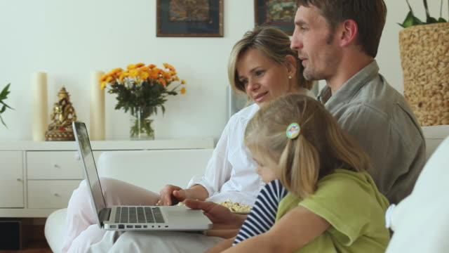 ms parents and daughter (4-5) sitting on sofa and looking at laptop together / potsdam, brandenburg, germany - beide elternteile stock-videos und b-roll-filmmaterial