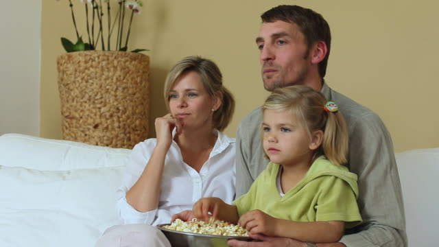 MS DS Parents and daughter (4-5) watching TV and eating popcorn / Potsdam, Brandenburg, Germany