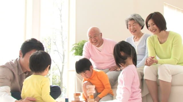 Parents and grandparents watching children playing with blocks