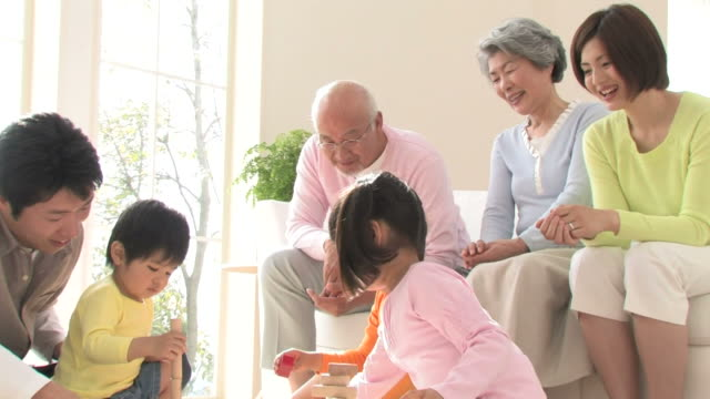 ZO Parents and grandparents watching children playing with blocks