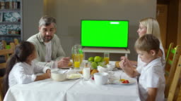 Parents and Kids Talking and Watching TV at Breakfast
