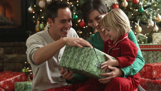 parents and little girl opening a christmas present - pacific islander family stock videos & royalty-free footage