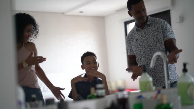 vidéos et rushes de parents et fils dansant devant le miroir à la maison - salle de bain