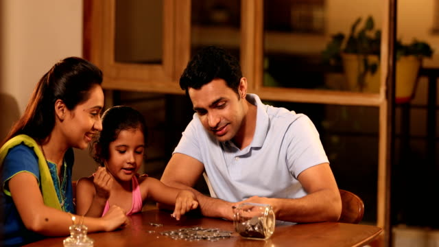 stockvideo's en b-roll-footage met ms pan parents and their daughter counting coins on table at home / sonipat, haryana, india - glazen pot
