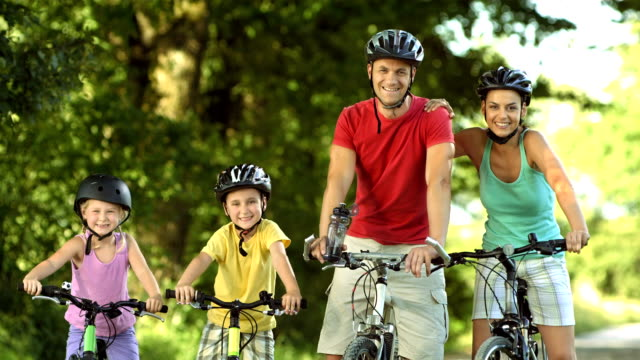 hd: parents and their two children on bicycles - cycling helmet stock videos & royalty-free footage